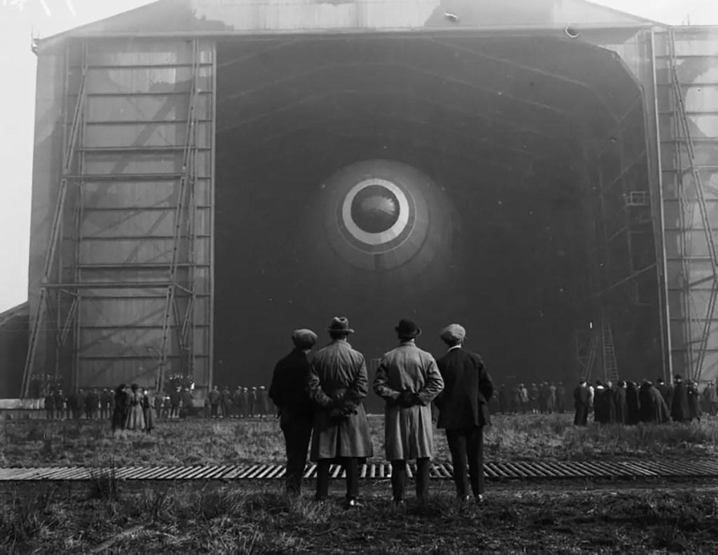 Fotografía de un grupo de personas viendo a un dirigible salir de un hangar.