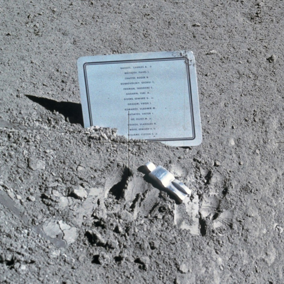 Fotografía en la superficie lunar de la placa a los astronautas caídos junto al monumento lunar.