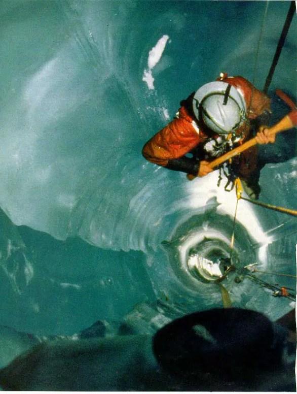 Hombvre bajando por una caverna de hielo.