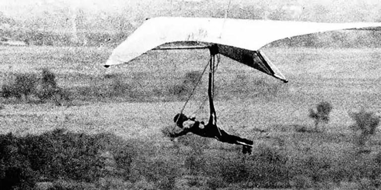 Fotografía antigua de un hombre volando en un ala delta.