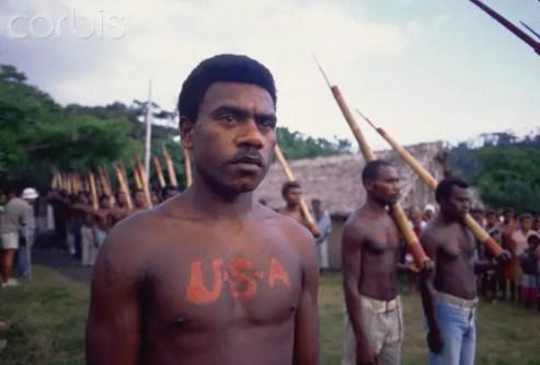 """Fotografía de un hombre de la tribu con las siglas USA escritas en su pecho uno de los """"cargo cults"""" más famosos del mundo."""