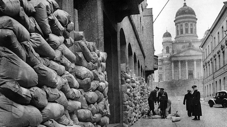 Fotografía de un grupo de hombres colocando bolsas de arena en las fachadas de edificios.