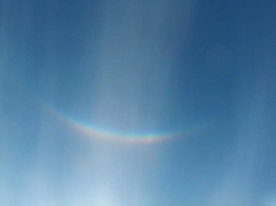 Fotografía de un arco iris invertido en el cielo.