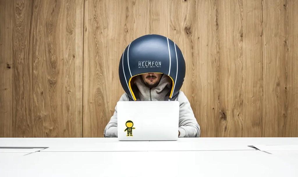 Un hombre vistiendo un Helmfon mientras utiliza su ordenador portátil.