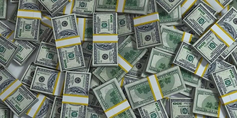 Varios fajos de dólares desparramados sobre una mesa.