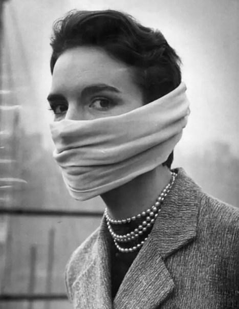 Mujer vistiendo un barbijo en medio del smog.