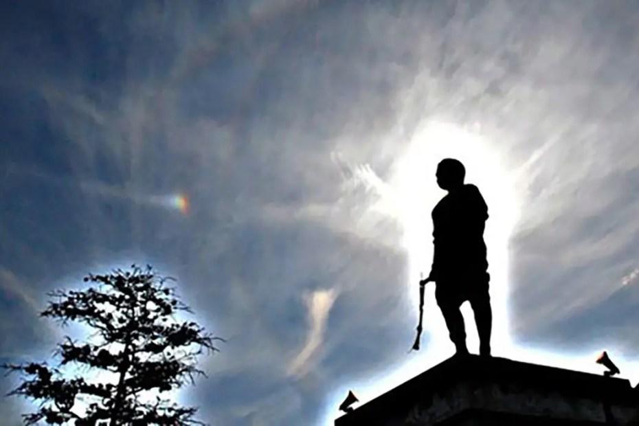 Silueta de una persona parada entre el lente de una cámara y un arco de Parry.