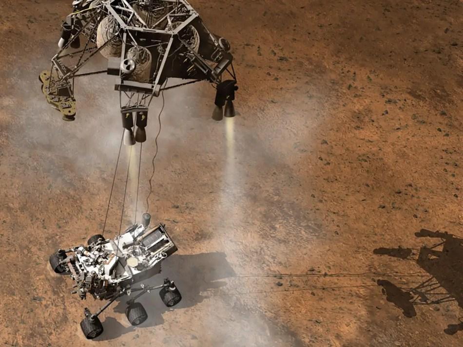Imagen por ordenador del dispositivo Sky Crane depositando a Curiosity en la superficie de Marte.
