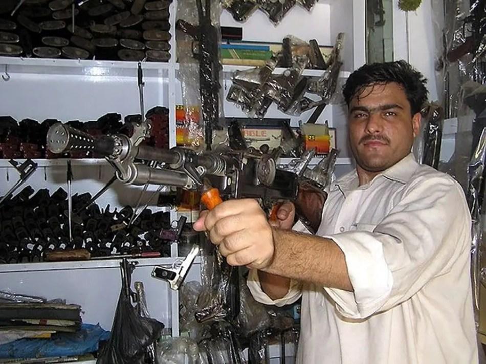 Vendedor mostrando una de las ametralladores a la venta.