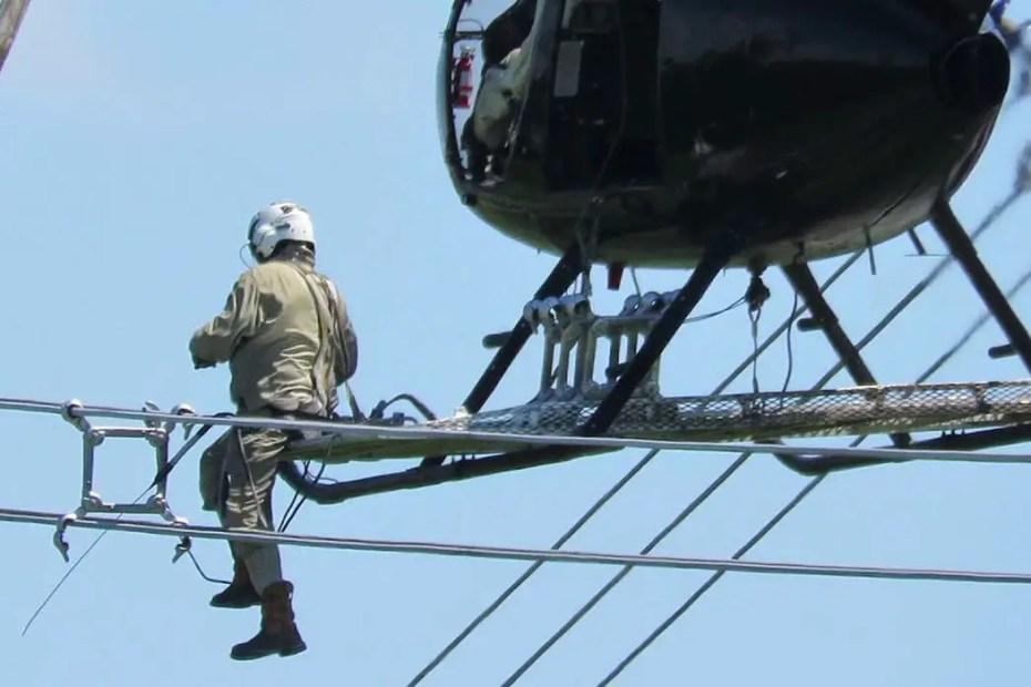 Trabajador reparando lineas de alto voltaje desde un helicóptero.