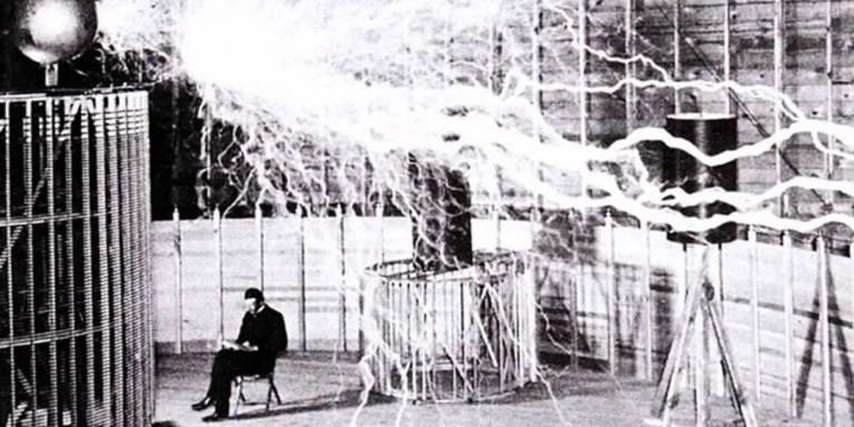 Nikola Tesla leyendo en su taller junto a una bobina eléctrica.
