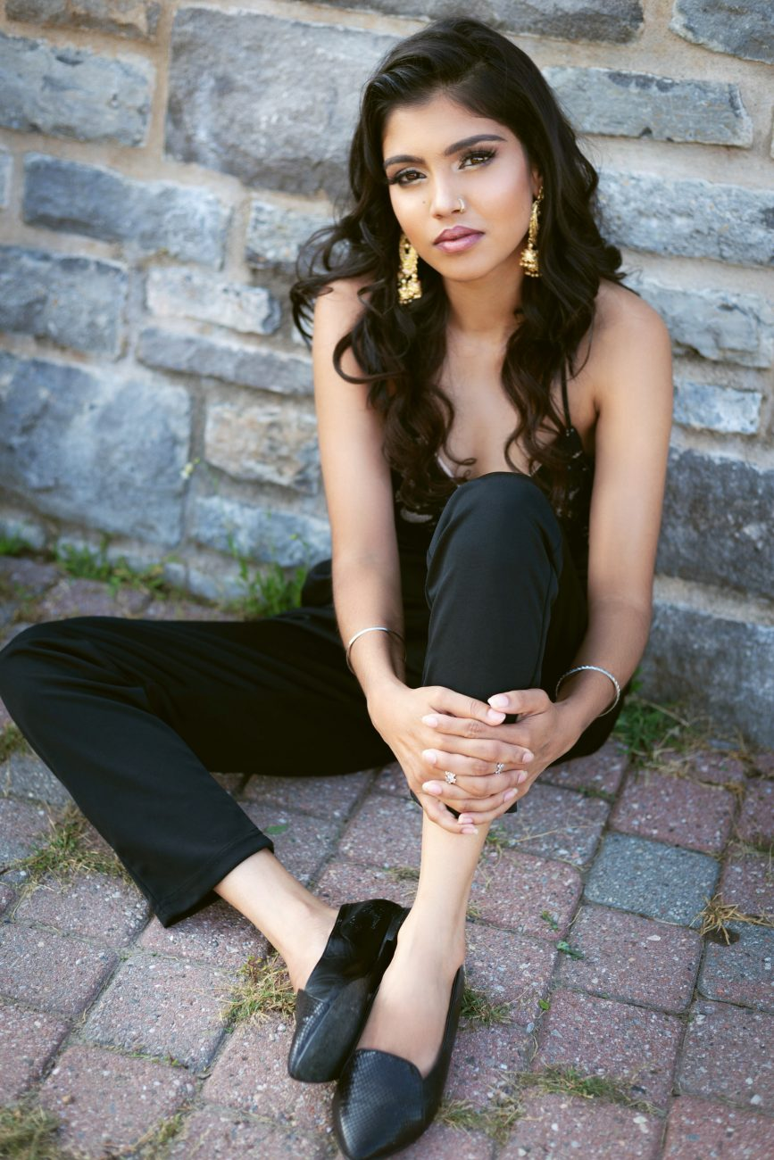 Indian model wearing fashionable clothing sitting in front of a brick wall