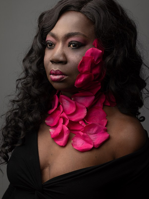 beauty portrait of a dark skinned model wearing vibrant pink roses