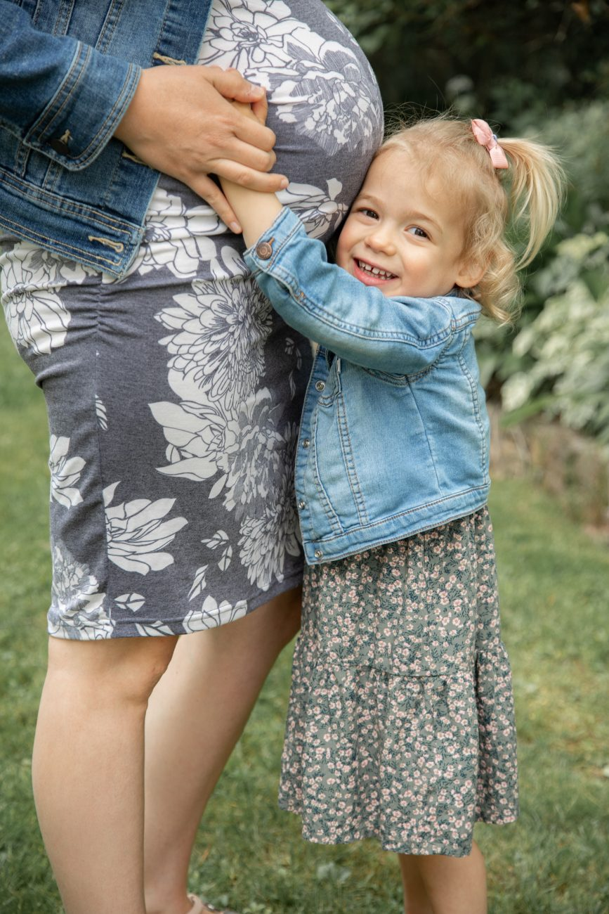 summer portrait of a young daughter hugging mom's pregnant tummy in Ottawa