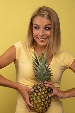 Smiling model holding a pineapple