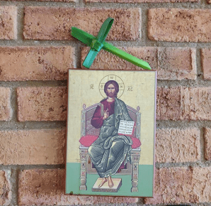 Icon of Christ on a brick wall. On top sits a palm cross made from a daffodil lead.