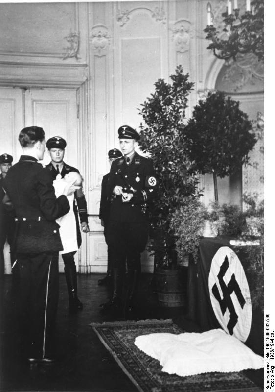 Un familiar hace entrega del niño a la causa, fé y creencias nazis