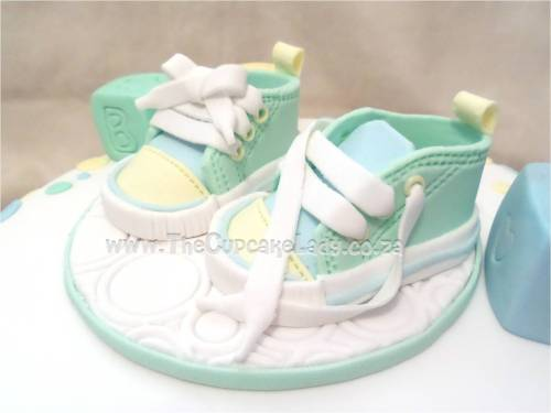red velvet cake with cream cheese icing, a green, yellow, and blue colour scheme with overlapping dots, baby blocks, and a pair of baby shoes
