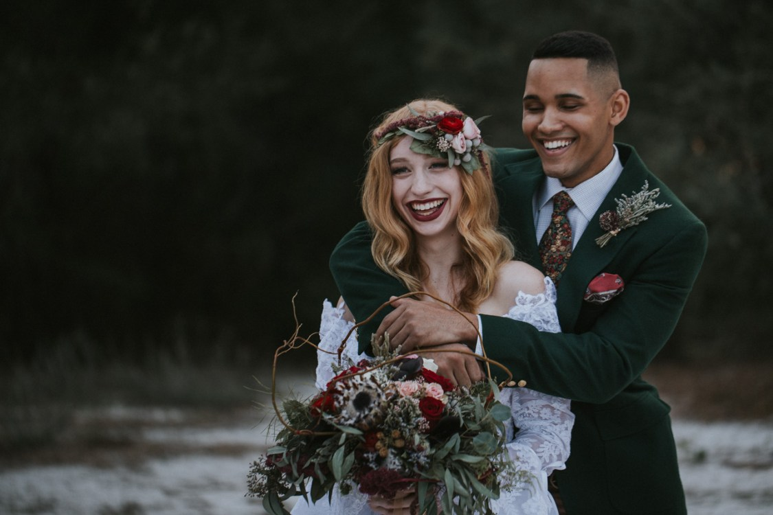 Bride and Groom smiling while bride wears a flower crown in Lake Runnymede conservation area in Saint Cloud Florida
