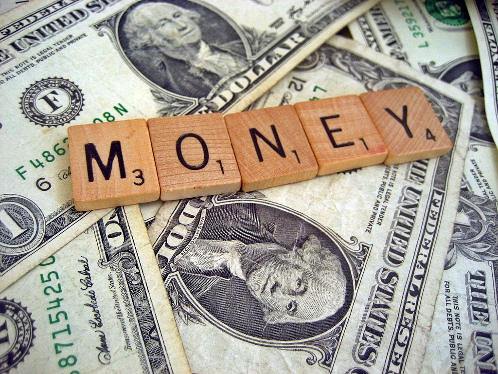 An image of dollar bills with Scrabble letters spelling out 'money' on top.