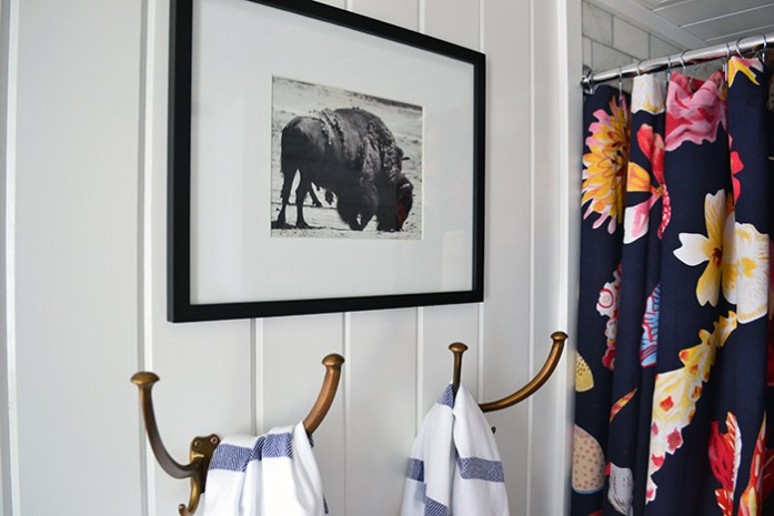Black and white buffalo art print hanging in a bathroom above vintage towel hooks and Turkish bath towels.