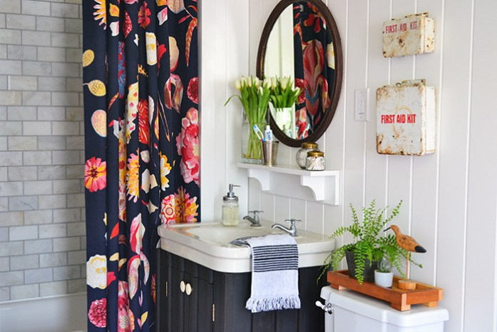 A bold Anthropologie shower curtain is the star of this farmhouse bathroom renovation. A vintage mirror hangs above a sink sitting on a dark painted vanity base. Vintage first aid kits hang above the toilet.