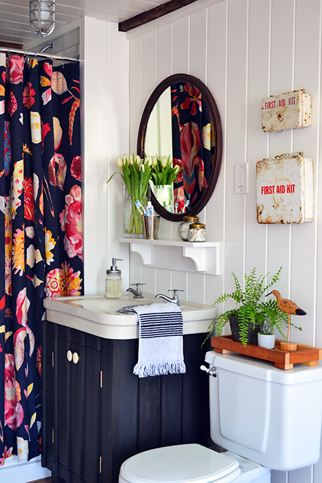 A guest bathroom renovation with a bold floral Anthropologie shower curtain, white planked walls, dark painted vanity, vintage white sink, copper mirror, and vintage first aid kits.