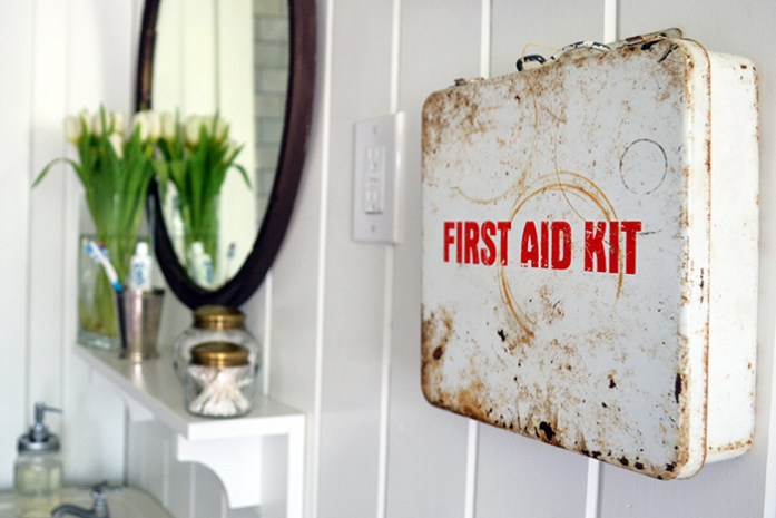 A metal, vintage first aid cabinet hangs above the toilet in this farmhouse bathroom.