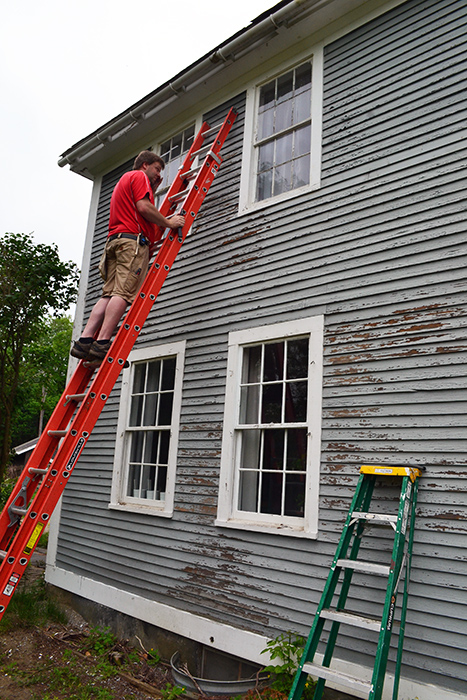 Scraping, repairing, and painting the clapboards of an old colonial farmhouse