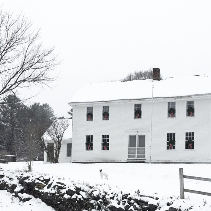 A white colonial farmhouse with Christmas wreaths on the windows for simple Christmas decor