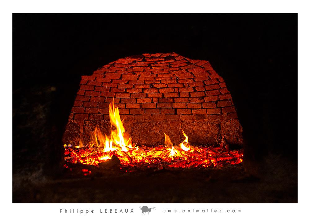 Le feu crépite dans le four à pain