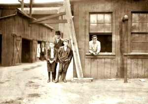 """""""These boys work off and on in the Cumberland Glass Works, Bridgeton, N.J. Smallest boy is George Cartwright, 401 N. Laurel Street. He says he has been working off and on since 11 years old."""" Photo by Lewis Hine, November 1909. Note the black stable hand in the background."""