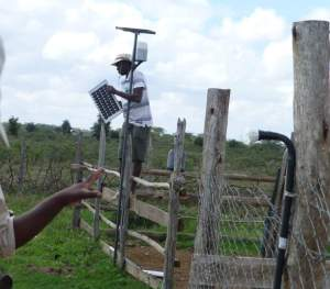 ANAW team installs a solar panel on a fence. (ANAW photo)