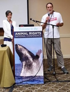 Talking about cats & dogs with Daphna Nachminovitch of PETA at the AR-2015 conference in Alexandria, Virginia, both unaware that the conference organizers had illustrated our presentation with a whale. (Beth Clifton photo)