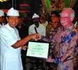 Bali governor Made Mangku Pastika accepts an award from FAO representative James McGrane. (FAO photo)