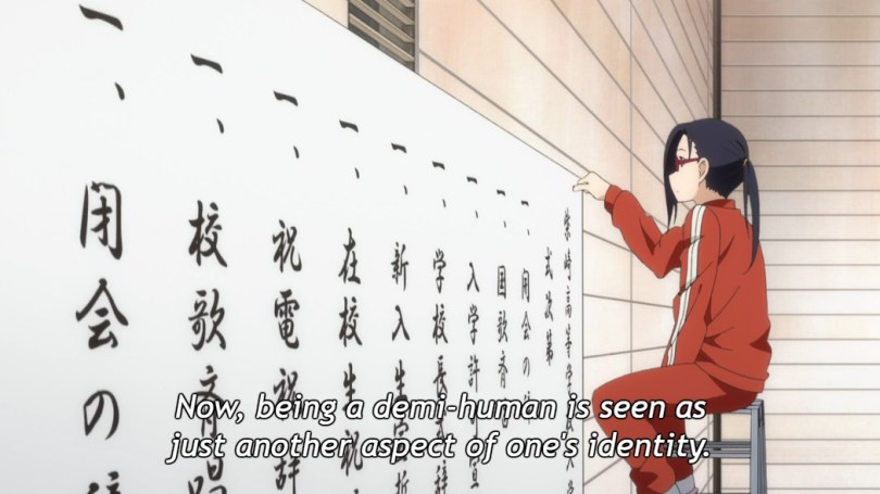"""Satou-sensei sits on a stool in her gym clothes, pinning a sign to the wall. Subtitle: """"Now, being a demi-human is seen as just another aspect of one's identity."""""""