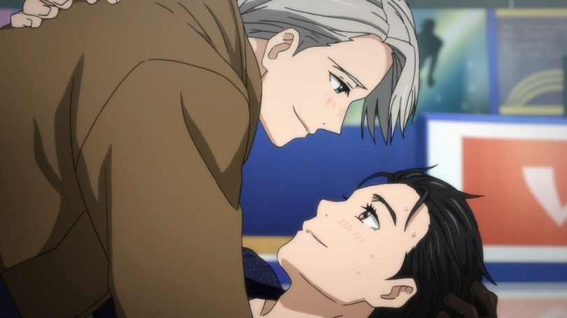 Victor, a man with short silver hair and wearing a brown coat, leans over and smiles affectionately down at black-haired Yuri, a young man who is looking up at him and smiling warmly back.