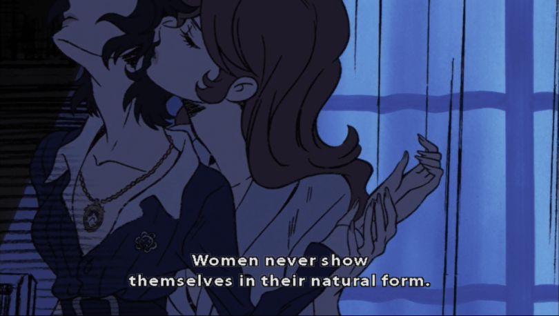Fujiko stands behind Isolde in The Woman Called Fujiko Mine, leaning into her neck as if to kiss it. Subtitle: Women never show themselves in their natural form.