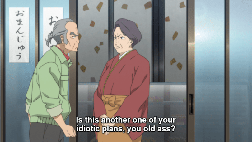 """An older woman in traditional Japanese clothing stands at the entrance of a Japanese sweet shop, looking stern as the grumpy Mr. Kadota walks past. Subtitle: """"Is this another one of your idiotic plans, you old ass?"""""""