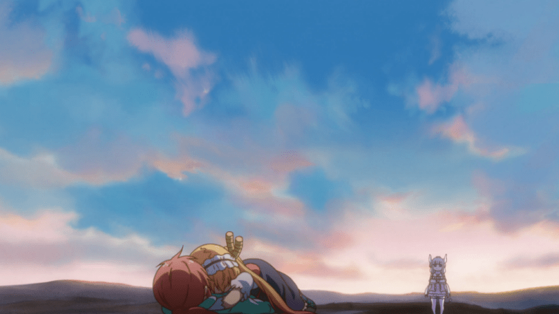 Tohru embracing Kobayashi on the ground with the sun rising behind them