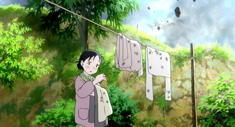 A girl picks ash off a shirt, a laundry line above her also covered in ash, while more falls from the sky