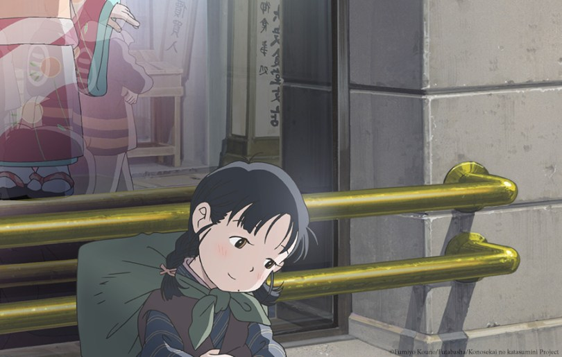 A girl in pigtails with a pack on her back sits in front of a store window, glancing down and smiling slightly