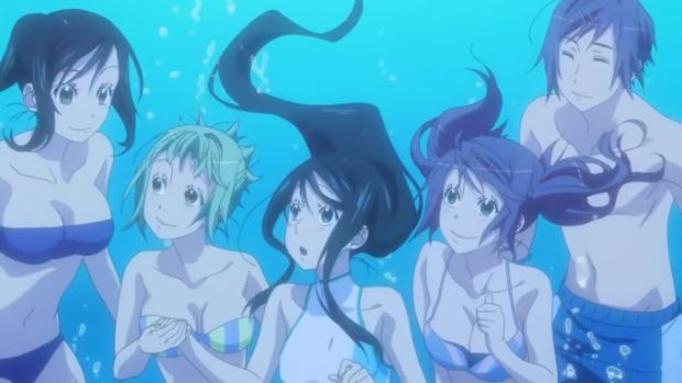 Underwater, three girls and a boy in swimsuits gather around another girl in the center; she looks shocked while they smile at her