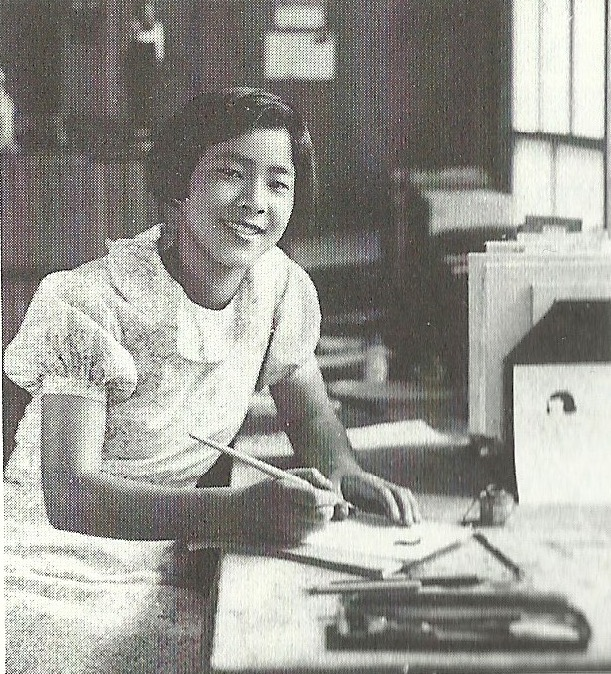 A black-and-white photo of a Japanese woman with bobbed hair wearing a dress with poofy sleeves. She has an ink pen in one hand and is sitting at a desk covered in papers.