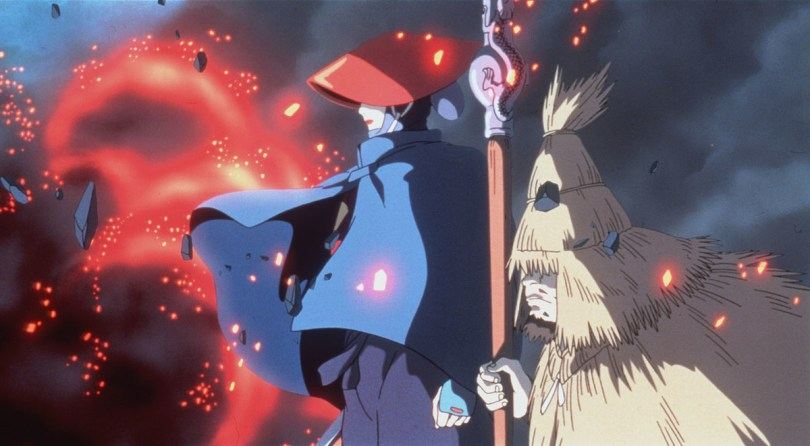 Eboshi, wearing a cloack and hat, looks out over red and smoky flames with a straw-cloaked man at her side