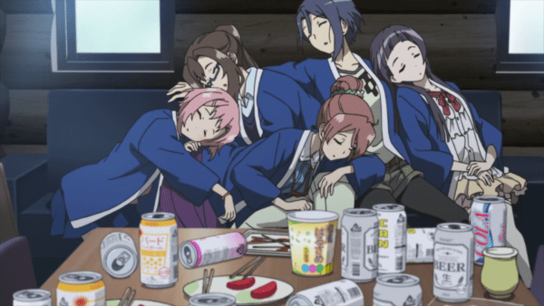 Five young women in onsen robes collapsed together into a sleeping pile. A table full of empty junk food containers is in front of them