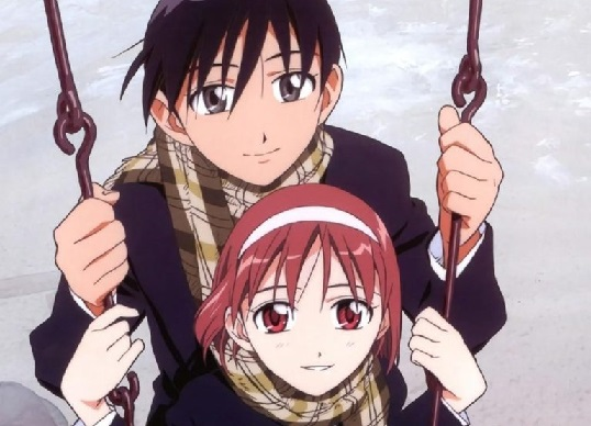 A girl sitting on a swing with both hands on the chain;a boy stands behind her, also holding the chain. Both are looking to the camera.