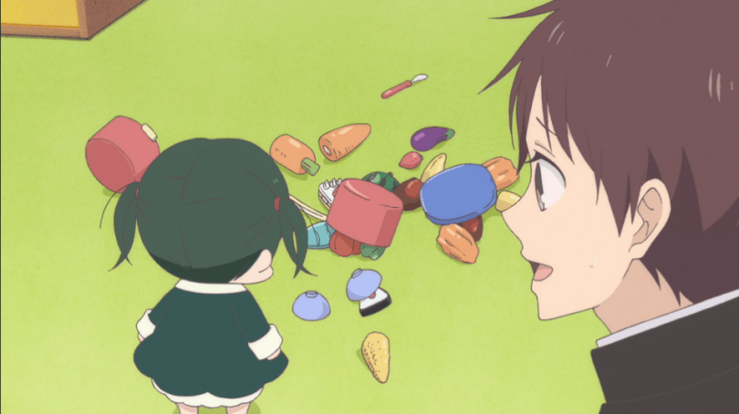 A teen boy looks at a little girl, her back to the camera, as she stares at a pile of fake food lying haphazardly across the floor.