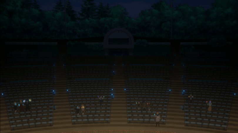 A long shot of a dimly lit theatre sparsely populated with audience members holding glowsticks.