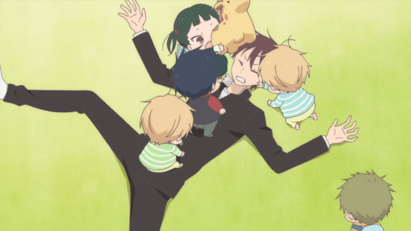 A teen boy in a black suit lays on the floor as four toddlers clamber on top of him, along with a plush giraffe.